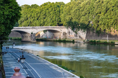 The Tiber is a river like all rivers except that it is in Rome, famous in its own right, has fifty foot walls, wide asphalt path on the west bank, many famous bridges over it, and is the eternal in the city of Rome.